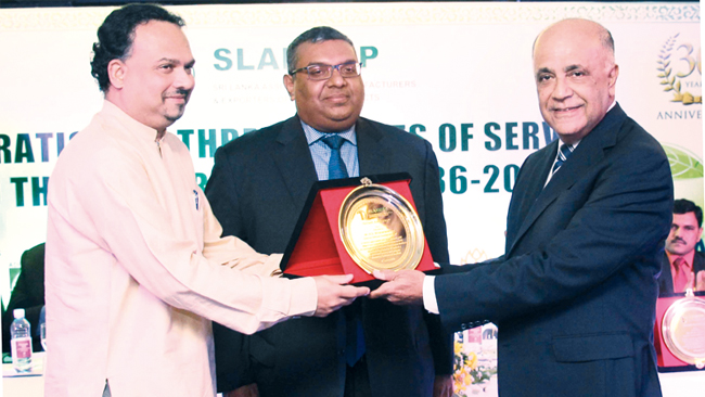 N. G  Wickramaratne founder Chairman of SLAMERP being presented a award to appreciate the dynamic leadership and guidance  provided by him by  Minister of Plantation Industries Navin Dissanayake, looked on by SLAMERP Chairman Prabhash Subasinghe. Picture by Saliya Rupasinghe