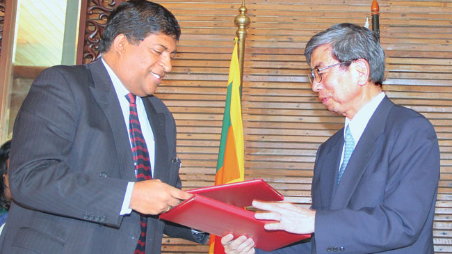 Visiting ADB President Takehiko Nakao signed several agreements.He is exchanging an agreement with Finance Minister Ravi Karunanayake.Picture by Samantha Weerasiri