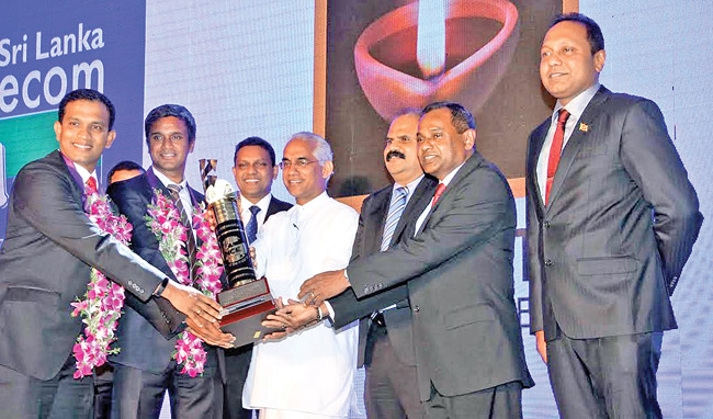 Richard Pieris, Natural Foams Limited won the Most Outstanding Exporter for 2015 year award at the annual NCE Exports awards held in Colombo Hilton last Friday. Here Public Enterprises Development, Deputy Minister Eran Wickramaratne is seen presenting the Most Outstanding Exporter of theYear 2015 trophy to Richard Pieris, Natural Foams Limited. Chairman Sri Lanka Telecom. P.G. Kumarasinghe, Sarada De Silva, President of the Chamber, Shiham Marikar, Secretary General/CEO look on. Picture by Sulochana Gamage.
