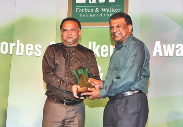 Plantation Industries Minister Navin Dissanayake presenting an award to  Kelani Valley Plantations and Talawakelle Tea Estates Managing Director Roshan Rajadurai at the Forbes and Walker Tea Awards 2016.