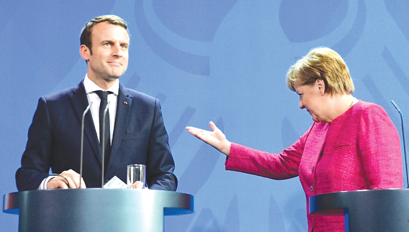 German Chancellor Angela Merkel gestures to French President Emmanuel Macron after addressing a press conference at the chancellery in Berlin on Monday. - AFP