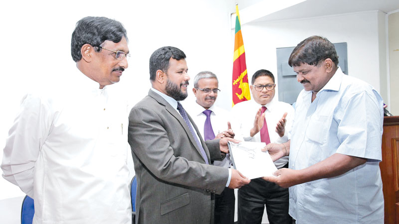 Minister of Industry and Commerce Rishad Bathiudeen handing over a certificate to an SME businessman.