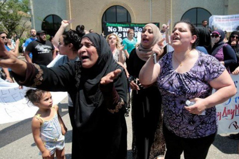 A group of women react as they talk about family members seized on Sunday by Immigration and Customs Enforcement agents during a rally outside the Mother of God Catholic Chaldean church in Southfield, Michigan, US on Monday.