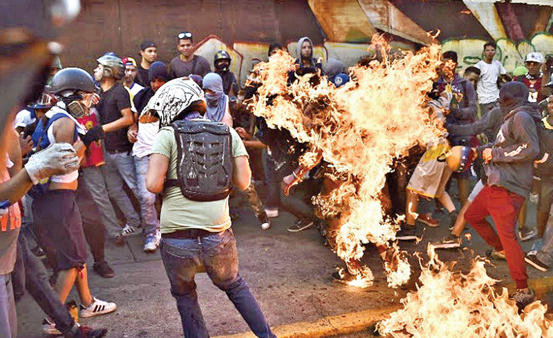 This file photo taken on May 20, 2017 shows opposition demonstrators setting an alleged thief on fire during a protest against the government of President Nicolas Maduro in Caracas.-  AFP