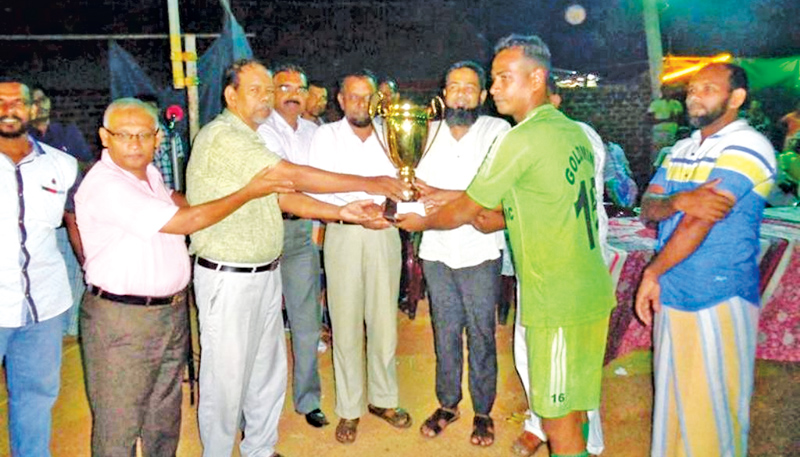The skipper of Maruthamunai Gold Mind Sports Club Football team receiving the trophy from Eastern Provincial Councilor Zibly Farook