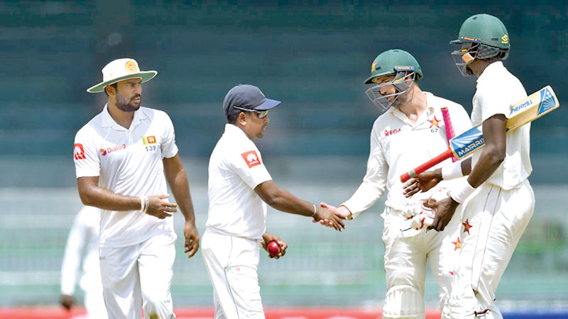 Zimbabwe captain Graeme Cremer shakes hands with Rangana Herath after the Lankan spinner had taken six wickets in the second innings and 11 in the match. AFP