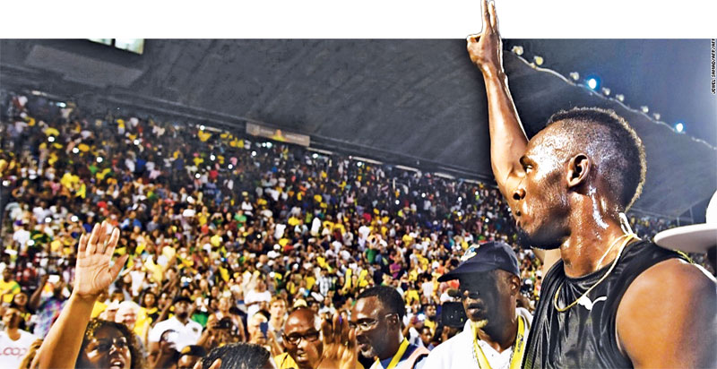"Usain Bolt of Jamaica salutes the crowd after winning 100m ""Salute to a Legend"" race during the Racers Grand Prix at the national stadium in Kingston"