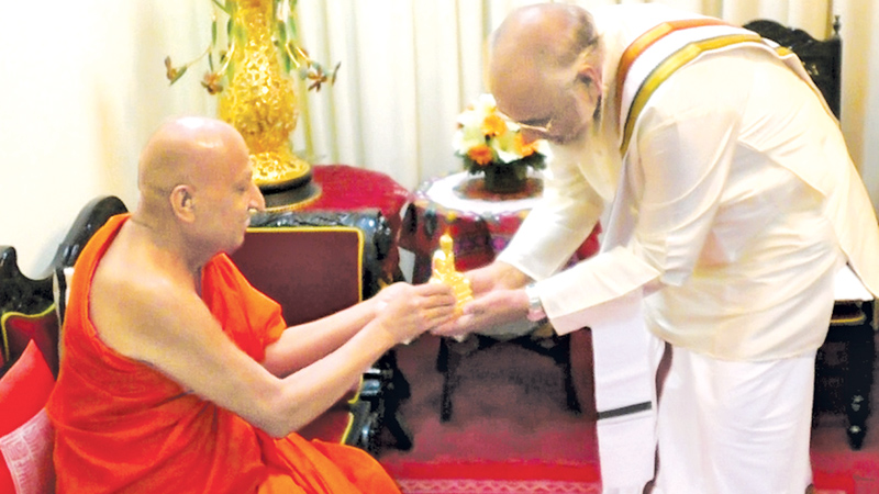 "The Most Ven. Tibbotuwawe Sri Siddhartha Sumangala Mahanayake Thera of the Malwatte Chapter presenting a ""Buddha statue"" as a memento to Northern Province Chief Minister C.V. Vigneshwaran when the latter called on him at his temple in Kandy and received his blessings recently. Picture by Udeni Rajapaksa"