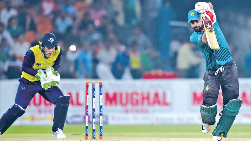 Pakistani batsman Ahmed Shahzad (R) plays a shot as World XI wicketerkeeper Tim Paine looks on during the first Twenty20 international match between the World XI and Pakistan at the Gaddafi Cricket Stadium in Lahore on September 12, 2017.  AFP