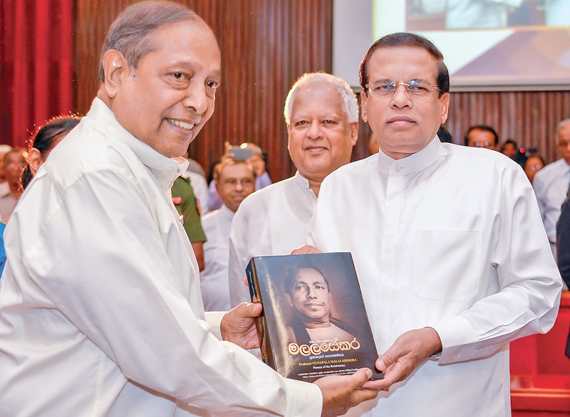 President Maithripala Sirisena presented with a copy of the biography of Prof. Gunapala Piyasena Malalasekara by Vijaya Malalasekara at an event held by the Malalasekara Foundation to commemorate the life of Prof. Malalasekara at the BMICH yesterday.  Picture by Nishanka de Silva