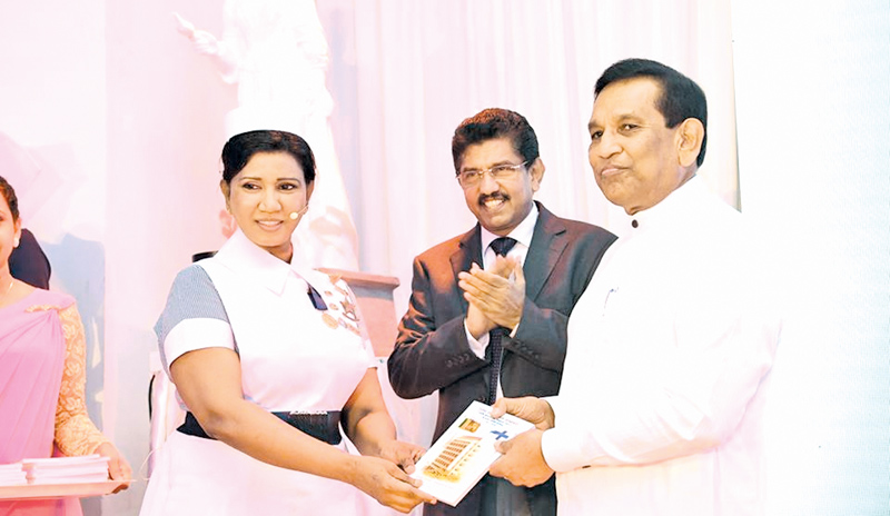 Health Minister Dr. Rajitha Senaratne being presented the book 'Rajatha Jayanthi Pelahara' by NHSL  Accident Ward National Training Officer Pushpa Ramyani De Zoysa, while NHSL Deputy Director General Dr. Anil Jasinghe looks on.