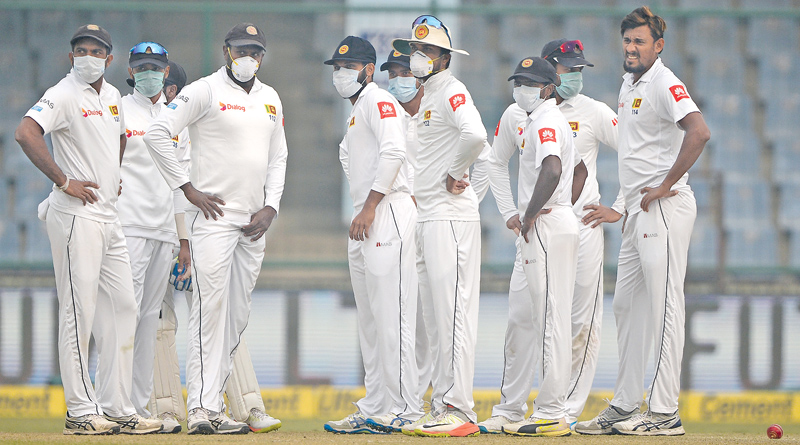 Sri Lankan fielders wore masks to prevent them from the smog in Delhi during India's second innings on the fourth day of the third and final cricket Test played at the Feroz Shah Kotla Stadium on Tuesday. AFP