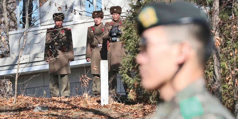 North Korean soldiers look at the South side as a South Korean stands guard near the spot where a North Korean soldier crossed the border on November 13 at Panmunjom, in the Demilitarized Zone, South Korea.