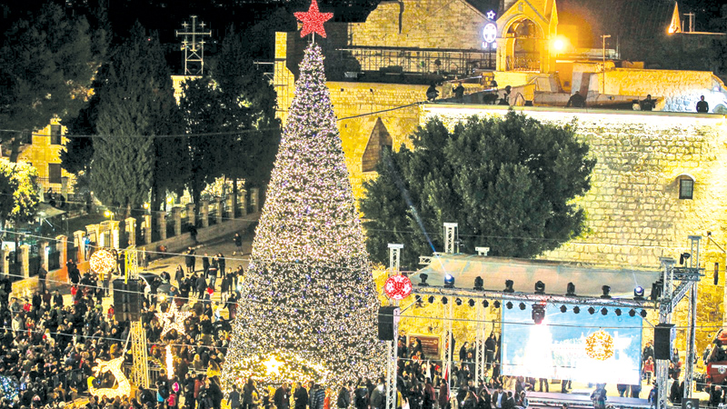 A picture taken on December 23, 2017 shows a general view of Christmas decorations in the Manger Square and the Church of the Nativity (back) in the Palestinian West Bank town of Bethlehem.
