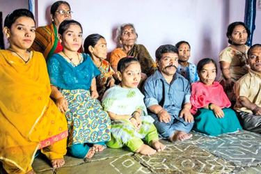 Ram Raj Chauhan and his family pose for a picture in their house