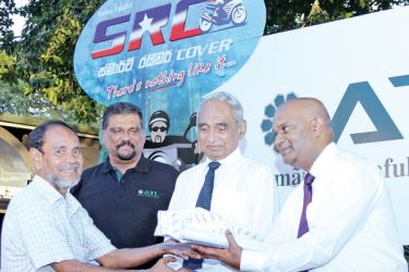Amana Takaful CEO Fazal Gafoor  is seen presenting a token to a policy holder.