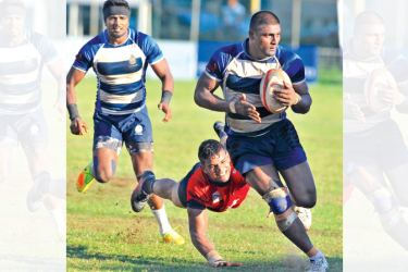 Navy SC centre Thanuja Maduranga evades a tackle from CR flanker Mithila Perera watched by Navy fly half Chanaka Chandimal (with head band) in the Dialog 'A' division league rugby match played at Longden Place yesterday. Pic Susantha Wijegunasekera