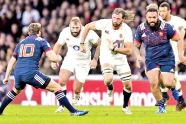 Tom Wood of England in action with Camille Lopez of France in their Six Nation rugby match at Twickenham Stadium on Saturday.