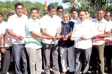 Minister Faiszer Musthapha opening the railroad crossing gate