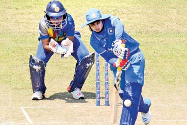 India Women's top scorer Devika Vaidya (89) drives for runs watched by Sri Lanka Women wicket-keeper Prasadani Weerakkody in their ICC Women's World Cup qualifier match played at the P Sara Oval yesterday. (Pix by Rukmal Gamage)