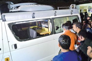 People look into a damaged TV news channel van after an assault in Karachi on Sunday. - AFP