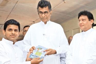 Handing the first copy of the book to Megapolis and Western Development Minister Patali Champika Ranawaka