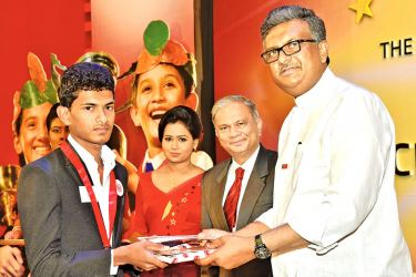 A student placed first in his district at the GCE Advanced Level examination receives his Pranama scholarship from Professor Sampath Amaratunge, Vice Chancellor of the University of Sri Jayewardenepura.
