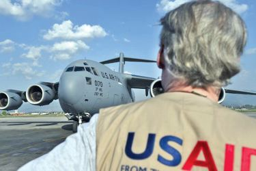 In this file photo, a USAID officer watches as a US military C-17 cargo plane taxis to a stop at Kathmandu's international airport on May 3, 2015. - AFP