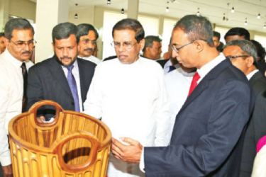President Maithripala Sirisena inspects an award winning  wooden vessel on display at Shilpa Abhimani Presidential Awards session  at Polgolla Kandy yesterday joined by Minister of Industry and Commerce  Rishad Bathiudeen (second from left) and State Minister of Industry and  Commerce Champika Premadasa (third from left).
