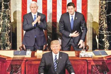 US President Donald Trump pauses as he speaks in front of Vice President Mike Pence (L) and Speaker of the House Paul Ryan at the Joint Session of Congress.