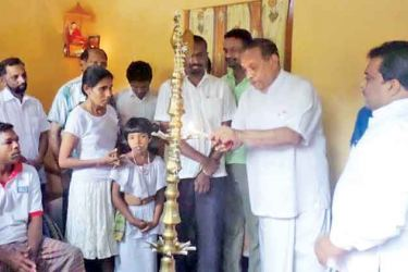 Speaker Karu Jayasuriya lighting the lamp auspiciously in the new house. Rupasinghe and his wife are also in the picture.