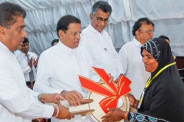 President Sirisena handing over the keys to a recipient