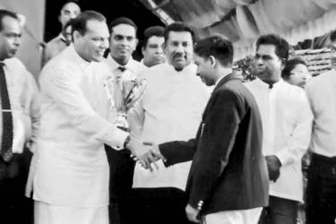 Dayasiri Jayasekara, Minister of Sports congratulating Dilshan Perera, the House captain of Abaya House at the inter house sports meet prior to him being presented with championship trophy. Also in the picture is  D Keerthi De Alwis, Principal.