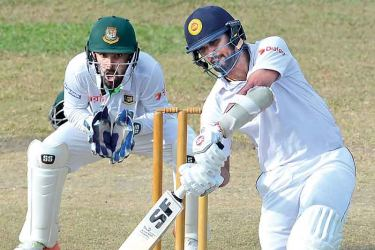 Sri Lanka President's XI skipper Dinesh Chandimal drives for runs watched by Bangladesh wicket-keeper Liton Das during his unbeaten innings of 190 in the two-day warm-up match played at Moratuwa yesterday. AFP