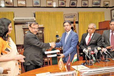 "Railways General Manager B.A.P. Ariyaratne and Indian 'RITES"" Company Executive Director Puneet Kumara exchanging documents after signing the MOU for the purchase of railway engines and power sets under an Indian government credit line. Indian High Commissioner Suja K. Menon and Sri Lanka railways officials were also present."