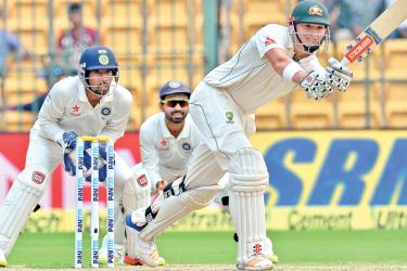 Australian batsman Matthew Renshaw drives watched by Indian wicket-keeper Wriddhiman Saha and slip Ajanke Rahane on the second day of the second Test at Bangalore on Sunday. AFP