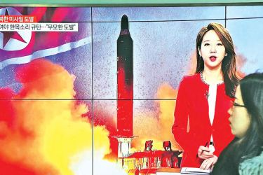 A women walks past a TV screen at a railway station in Seoul, South Korea yesterday broadcasting a news report on North Korea firing a ballistic missile into the sea off its east coast.