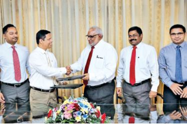 Commercial Bank Managing Director/CEO Jegan Durairatnam (fourth from right) exchanges the agreement with Mr Tilak Dias Gunasekara, Managing Director of Sathosa Motors in the presence of representatives of the senior and corporate management of the two institutions.