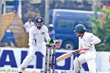 Bangladesh skipper Mushfiqur Rahim's fighting innings is ended by his rival captain Rangana Herath of Sri Lanka who bowls him for 85 on the third day of the first cricket Test at the Galle Stadium yesterday. Pix by Saman Mendis