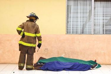 A firefighter looks at two of the 22 victims at a government-run children's shelter in San Jose Pinula after fire swept the building east of Guatemala City.