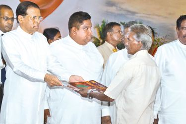 President Maithripala Sirisena distributing the title deed to  a resident