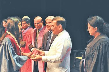 Health Minister Dr. Rajitha Senaratne hands over a degree certificate to a graduate while ministry officials look on