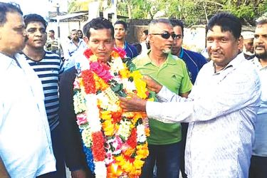 Champion athlete Siyad Mohamed being welcomed at his home town by the Principal of Km/Km/Al-Ashraq National School, Nintavur S.M.M.Jabeer while the Chief Inspector of Police M.L.Rafeek looks on. Picture by A. B. Abdul Gafoor, Ampara District Group Corr.