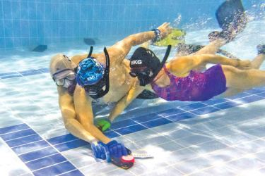 "In this photo taken on February 15, 2017, members of the ""HK Typhoon"" underwater hockey club fight for possession of the puck (front C) during their once-a-week team practise session at a 25-metre school pool in Hong Kong. - AFP"