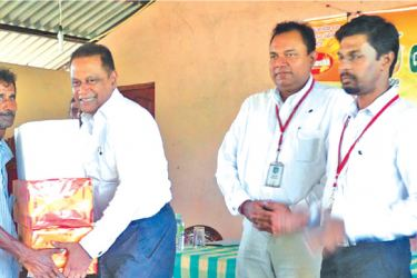 Plenty Foods Director and Chief Executive Officer Shammi Karunaratne handing over the provisions to a farmer  in the presence of General Manager Vasantha Chandrapala and Plenty Foods Agriculture Manager Preethiviraj.