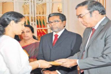 Foreign Affairs Ministry Secretary Esala Weerakoon awarding compensation to a beneficiary. Picture by Thushara Fernando