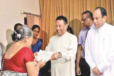 Social Empowerment and Welfare Minister S. B. Dissanayake handing over an appointment letter to a Divineguma Development Officer. Picture by PRIYAN DE SILVA