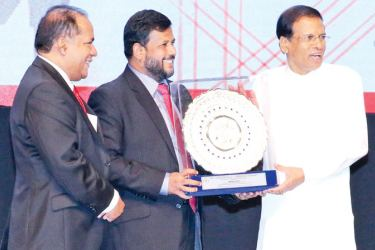 Industry and Commerce Minister Rishad Bathiudeen and CAA Chairman Hasitha Tillekaratne presenting the official souvenir to President Maithripala Sirisena at the Colombo celebration of World Consumer Rights Day held at the Nelum Pokuna Theatre.
