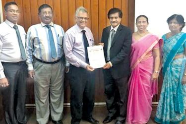 Geotech Testing Services  officials accepting the ISO 9001 certification from the Sri Lanka Standards Institution.