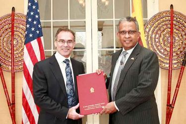 Ambassador Prasad Kariyawasam handing over the Commission of Appointment to David Bruce Sherman